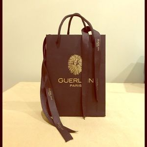 Guerlain paper bag with assorted ribbons.